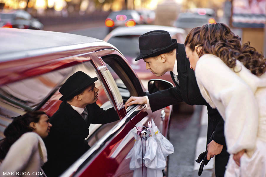The bride and groom want to sit in a red wedding limousine.