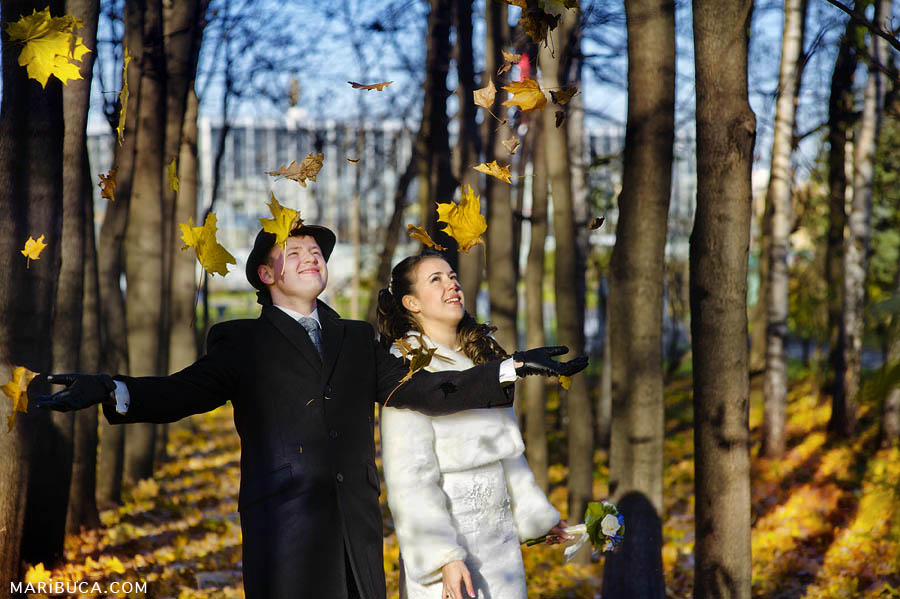 the bride and groom throw and enjoy falling yellow leaves surrounded by alleys of trees