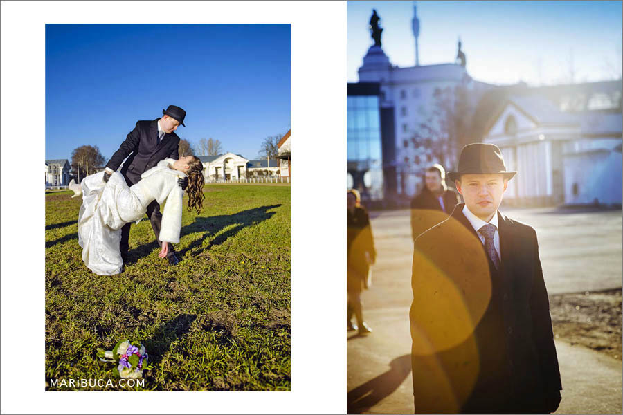 The bride and groom show the first dance on a photo walk. Portrait of the groom in a black hat and a black coat against the background of buildings.
