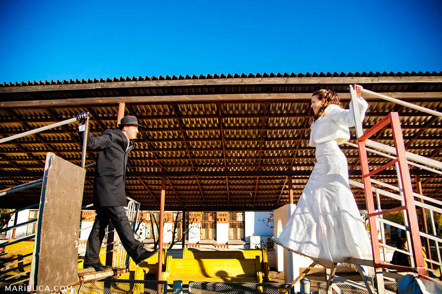 The bride and groom are drawn to each other in an industrial area.