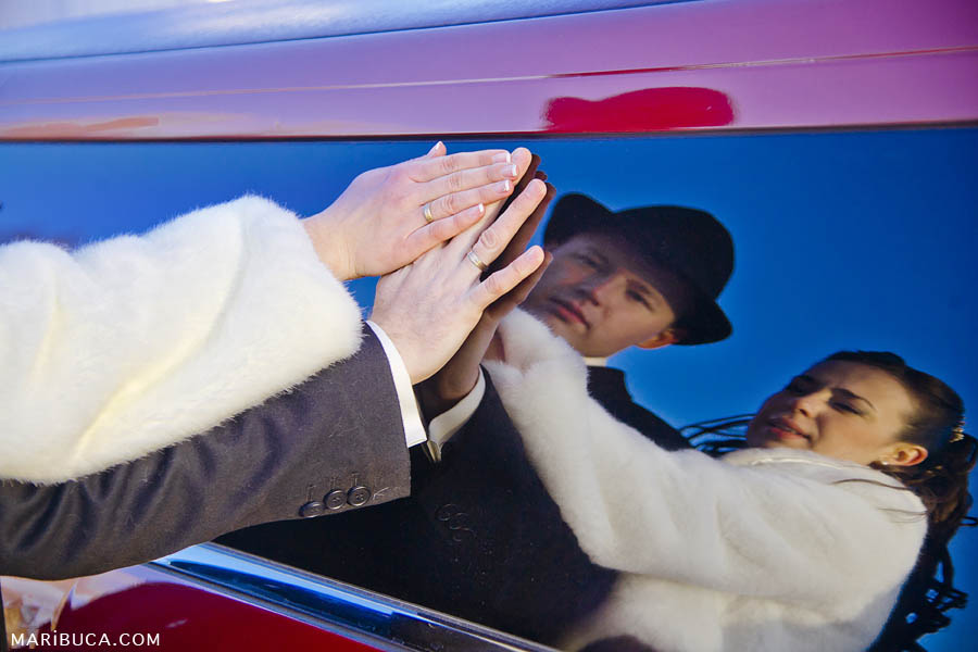 the bride and groom put his hands on the glass of red limousine and their faces can be seen in the reflection of the glass.
