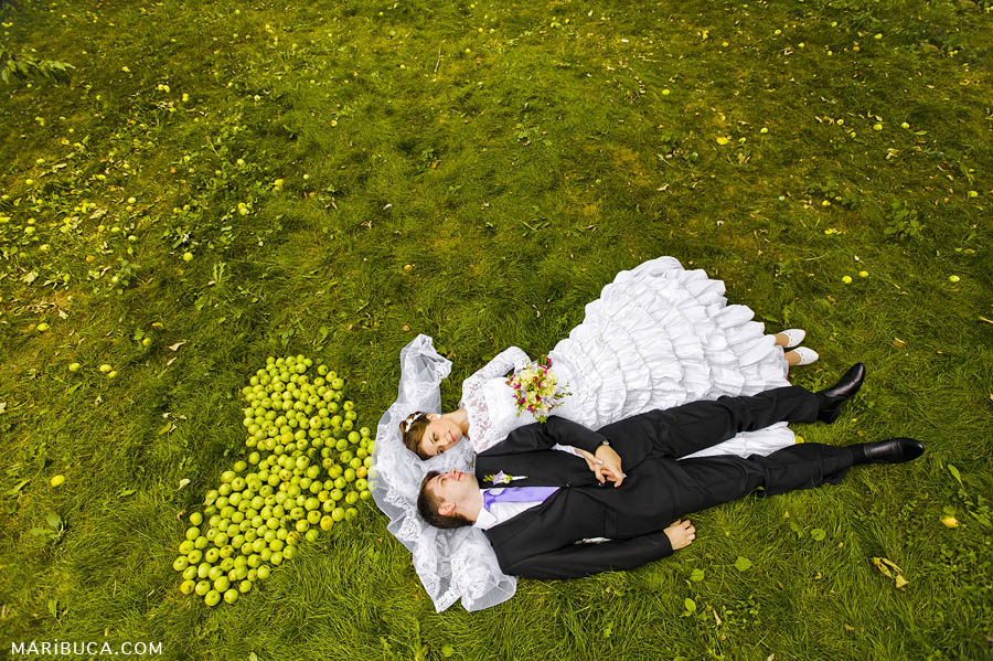 The bride and groom are laying down in the grass and the green apples shape there in the Los Altos