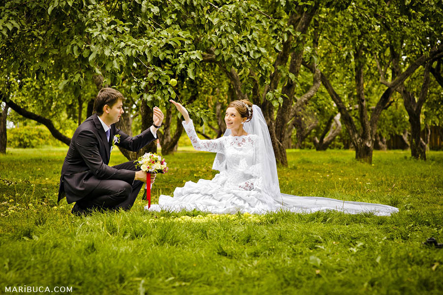 The groom and the bride play with green apple in an apples orchard garden
