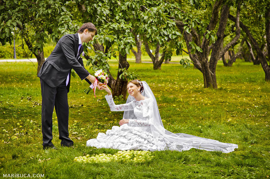 The groom and the bride are laughing in an apples orchard garden
