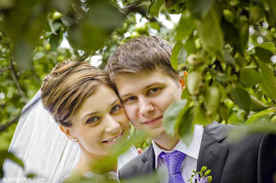 Bride and groom portrait in the apple green garden