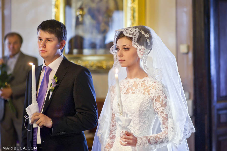 bride and groom stand with candles in a christian church