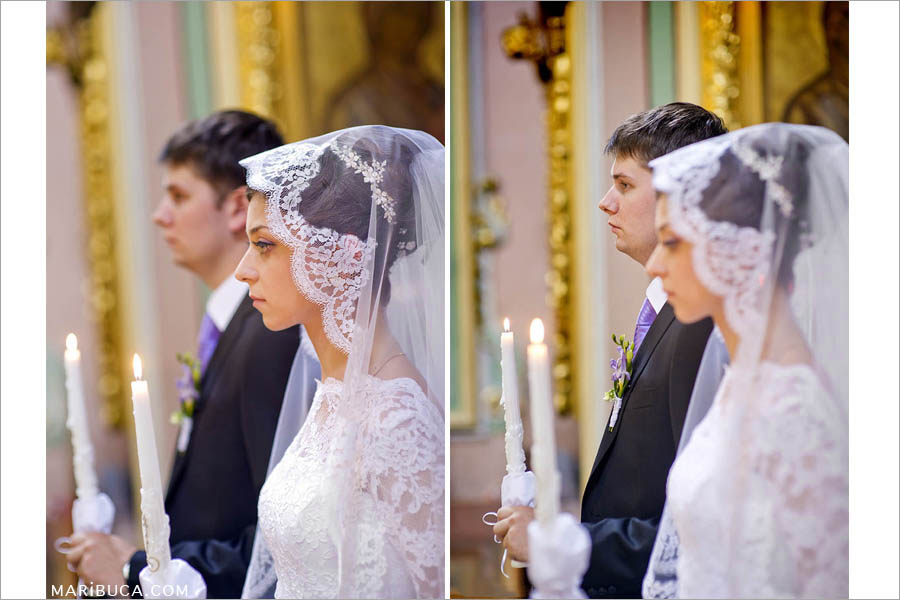 portrait of bride and groom holding candles in church with guests for a wedding ceremony in a christian church