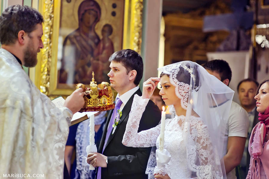 priest removes crowns from newlyweds at the end of a wedding ceremony in a Christian church
