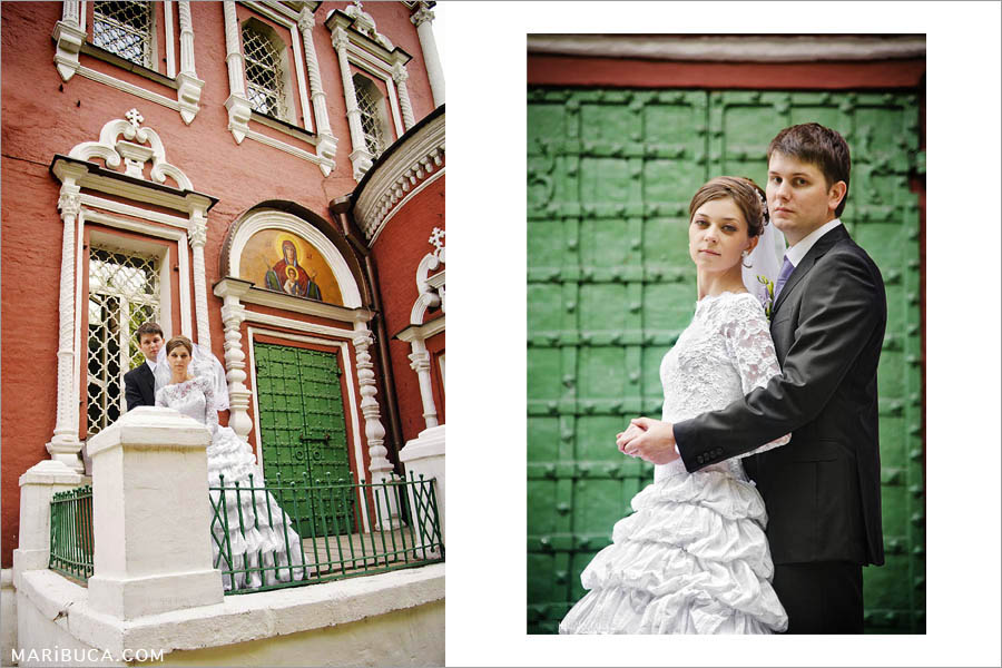 portrait of newlyweds near the church on the background of green metal doors and a red brick wall.