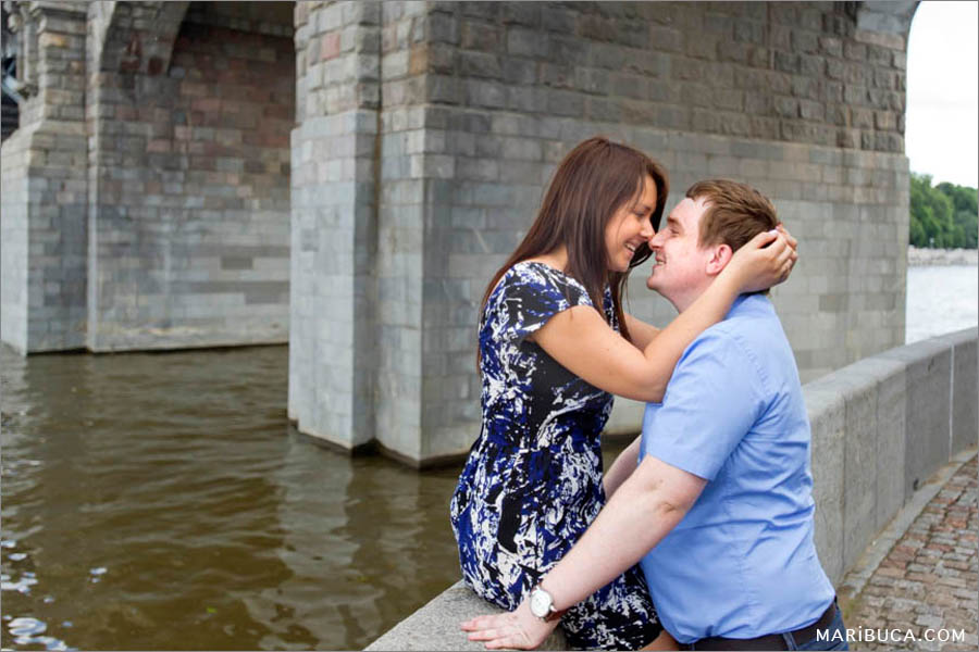 Girl and guy are smiling and kissing each other in the San Francisco bridge