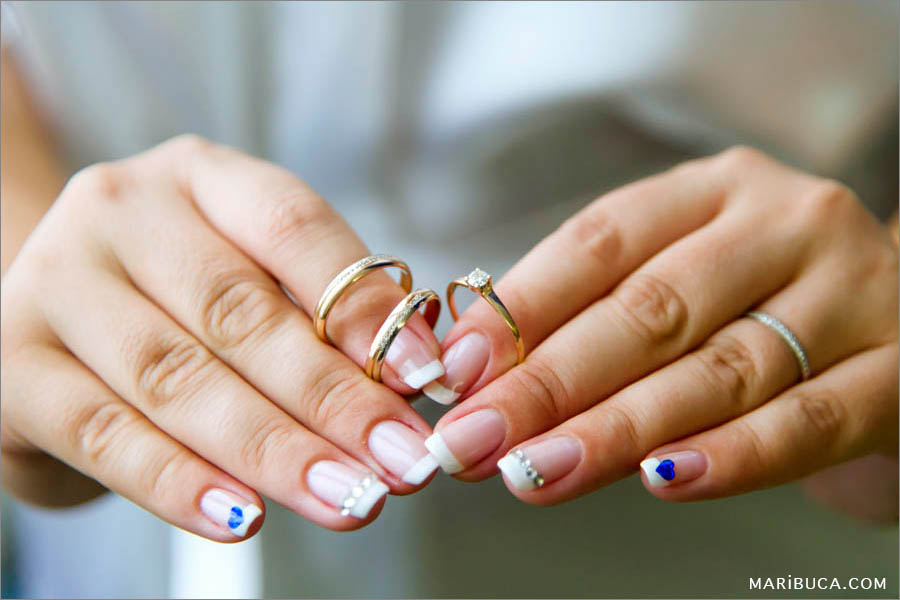 The bride's hand holding wedding rings and engagement ring