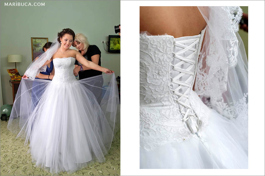 The bride shows her beautiful white wedding dress to the guests. The element of a white wedding dress is a corset.