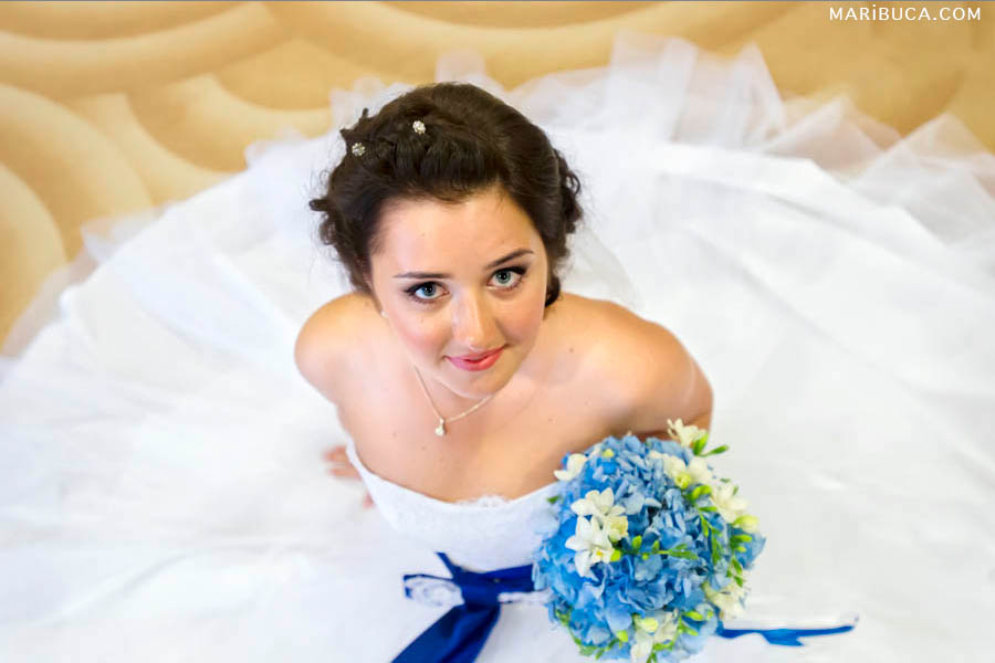 The bride is sitting in the yellow floor and look up. She has the beautiful white dress, navy blue belt and light blue flower.