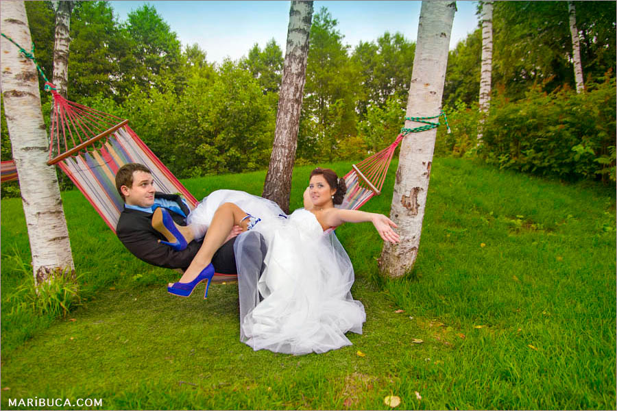 the bride and groom lying together in a hammock and enjoy their free time during the wedding day