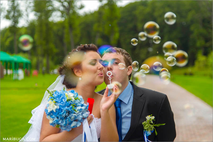 the bride and groom blow bubbles in the background golf club in California