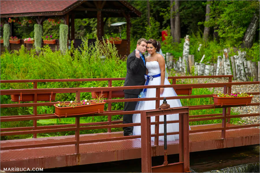 Newlyweds happy and they are standing in the brown wooden bridge in the green park.