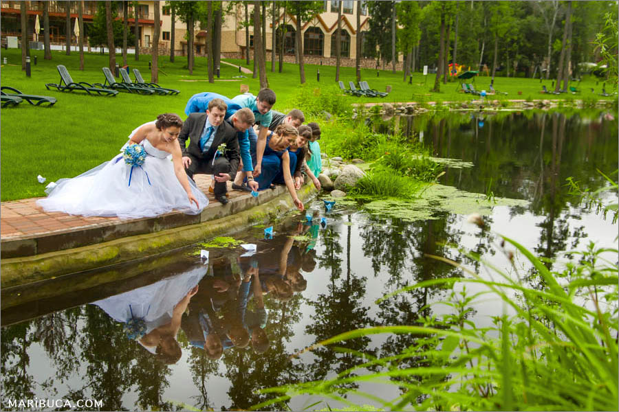 Wedding party, the bride and the groom has competition whos faster paper boat will be on the other side of the pond.