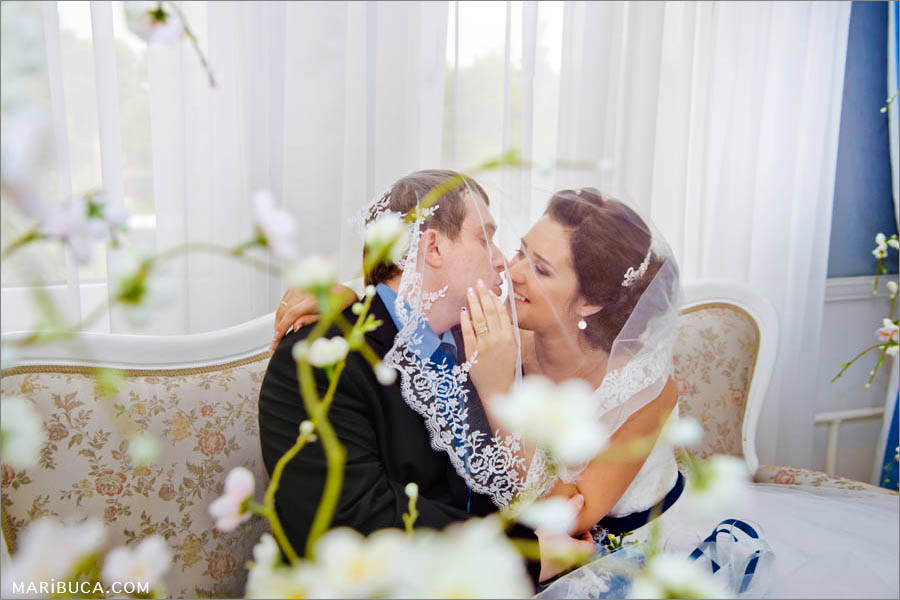 Moment when the bride and the groom are smiling and try to kiss each other under the white veil.