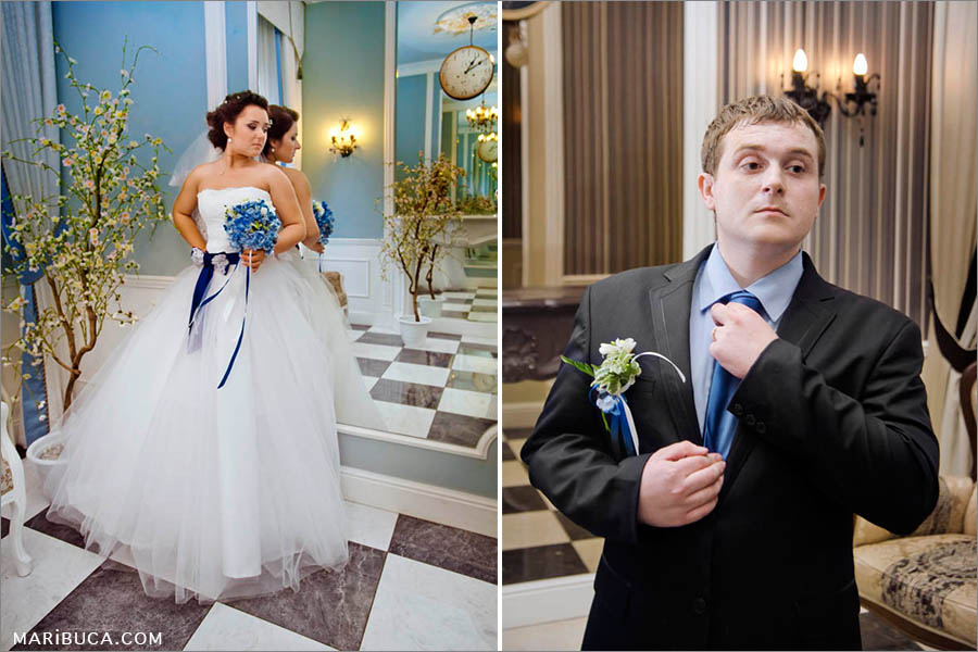 Portrait of the bride in the white dress and blue wedding bouquet, and the groom who looks in the mirror.