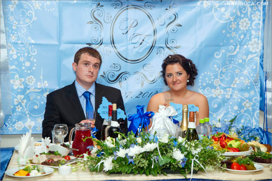 the newlyweds are sitting at the holiday table and a light blue backdrop with their initials