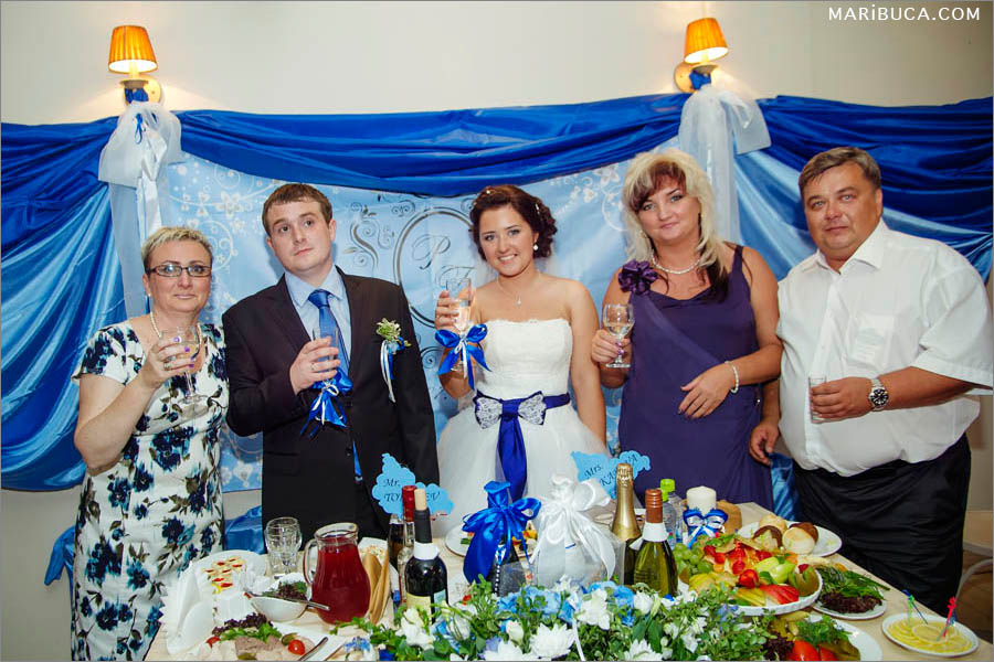 Group image newlyweds and parents and navy blue background