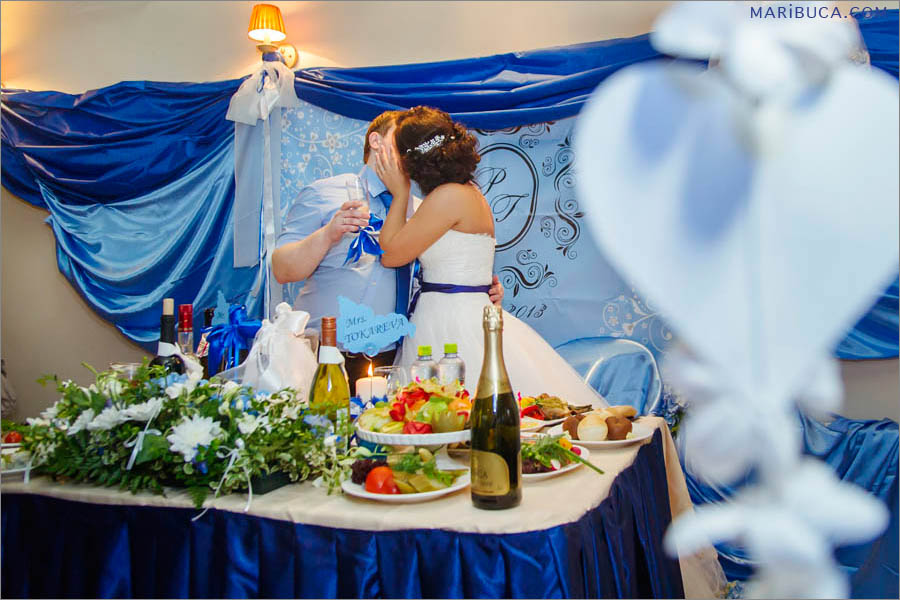 The bride and groom are kissing each other in the reception.