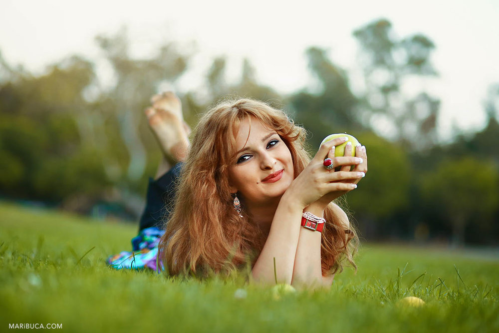 Happy girl lay downs in the green grass and holding the green apple in the Vasona Park, Los Gatos.