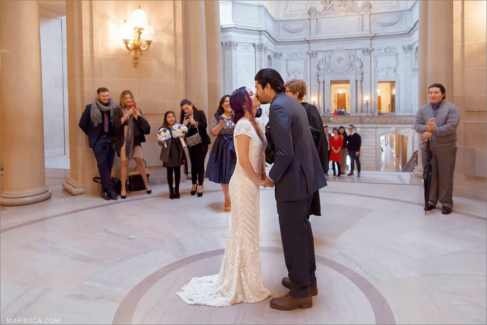 In the San Francisco City Hall, second floor the bride and groom are kissing each other, and their families and friends are taking pictures of them.