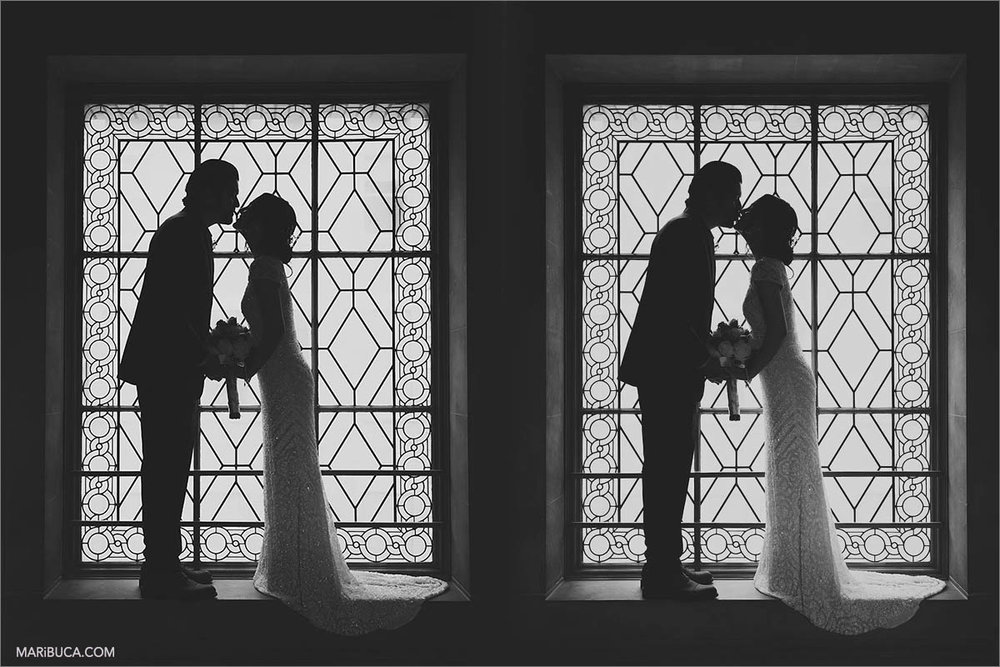 Silhouette of the bride and groom are kissing each other in front of the big window in the San Francisco City Hall.