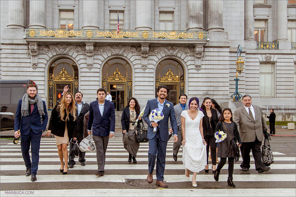 Family, friends and just married couple are going across the road and San Francisco City Hall in the background.