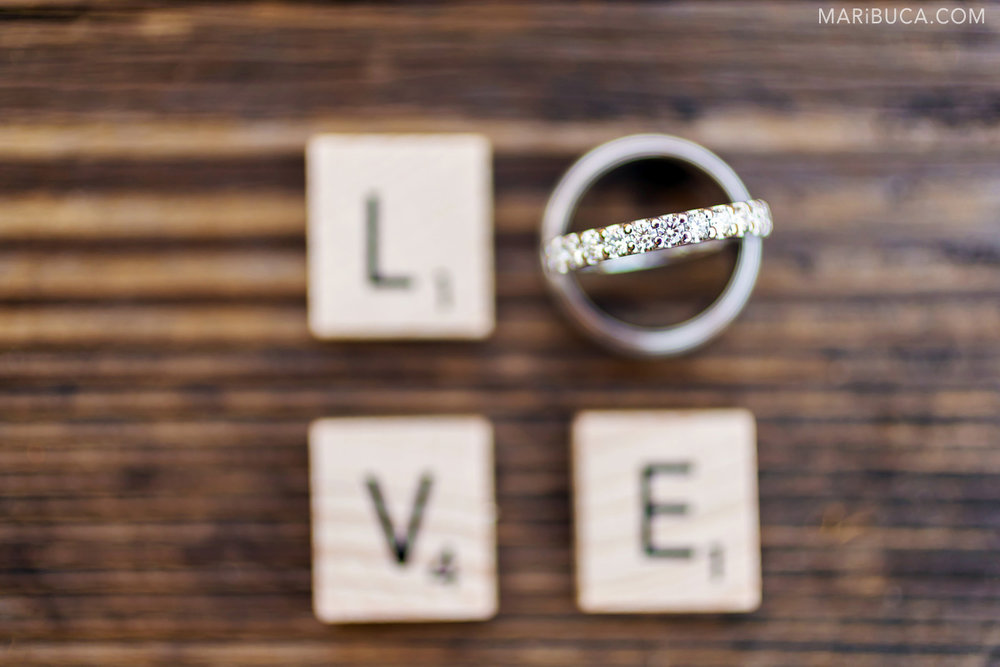 "The wood signs letters ""love"" and wedding rings as the symbol of LOVE and represent the letter ""O"" in the brown wood background."