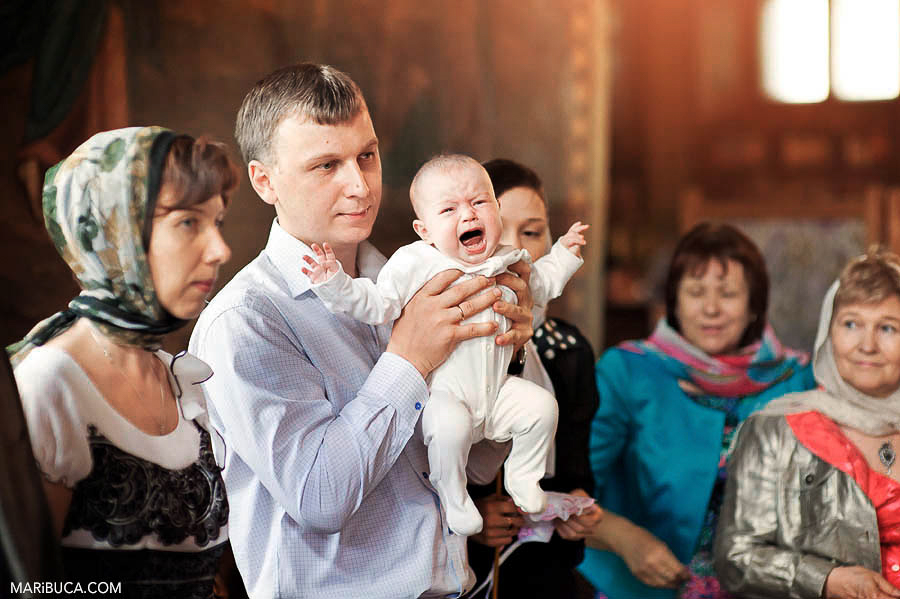 Family and friends during christening ceremony in the Russian orthodox church