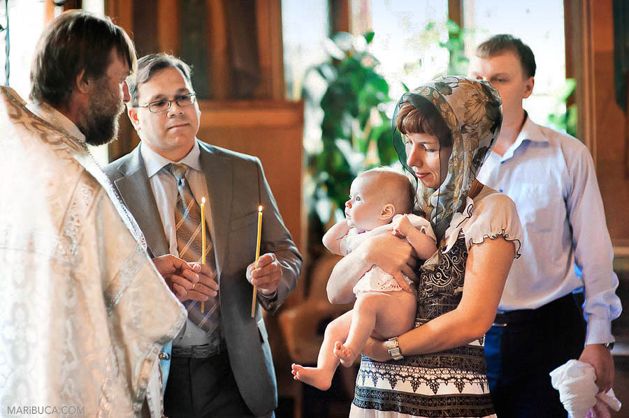 The godfather holds candles, the godmother holds baby girls and the priest pray for baby girl.
