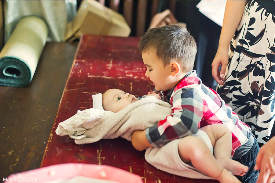 Older brother holds baby brother in the church before Christening in the church, California