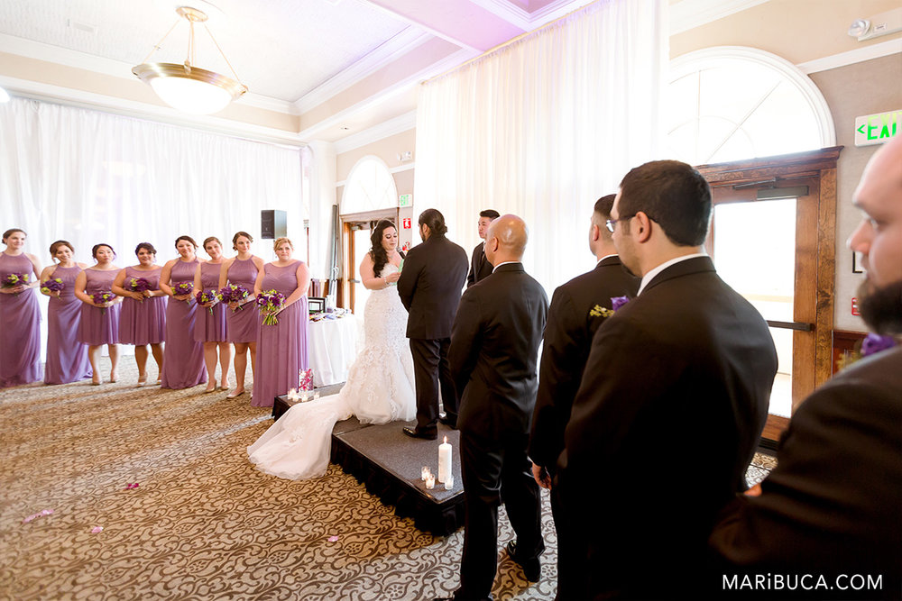 Bridal party and wedding couple during ceremony in the Traditional during wedding ceremony in the Villa Ragusa Campbell