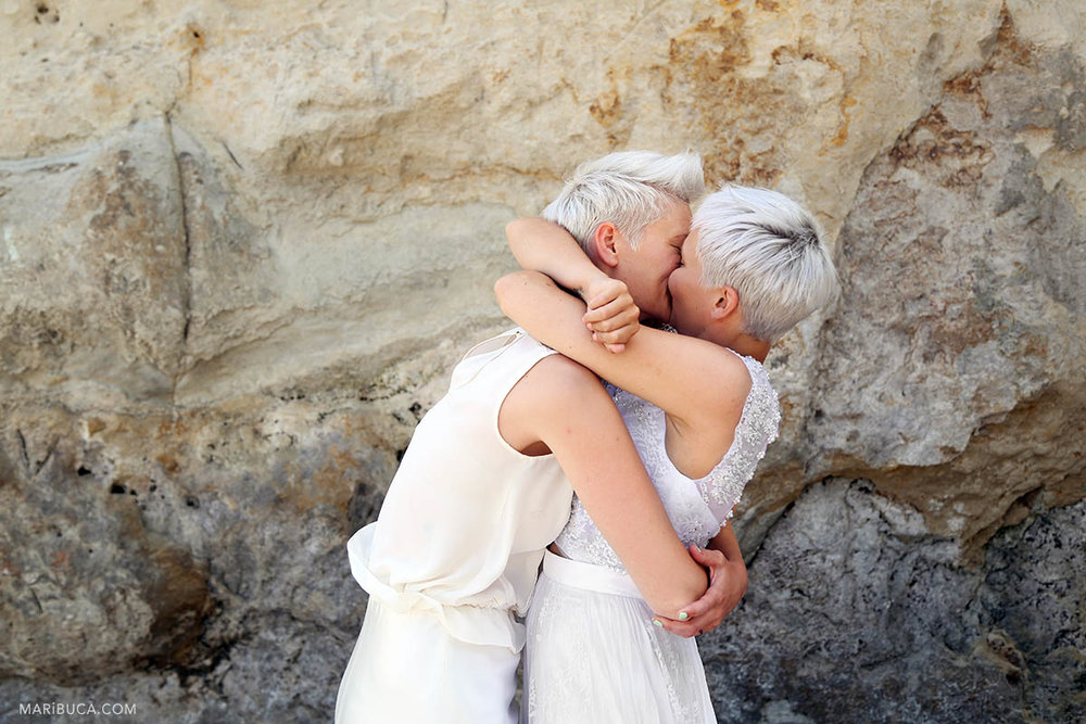 Beautiful brides kiss each other after wedding ceremony in the Cowell beach, Santa Cruz