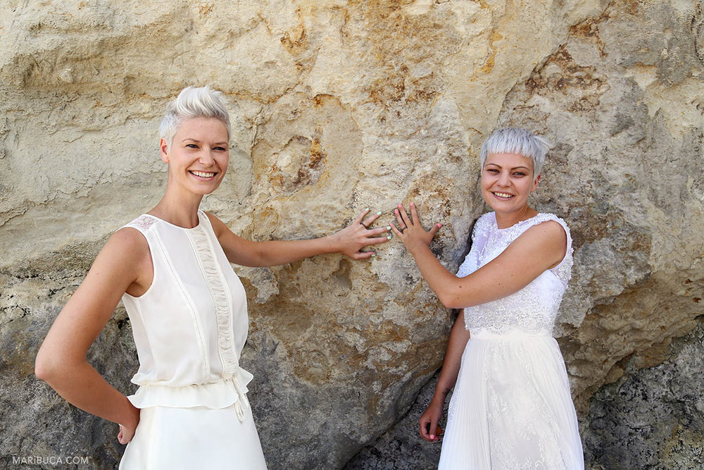 Two brides with white dresses and short haircuts posing for pictures.