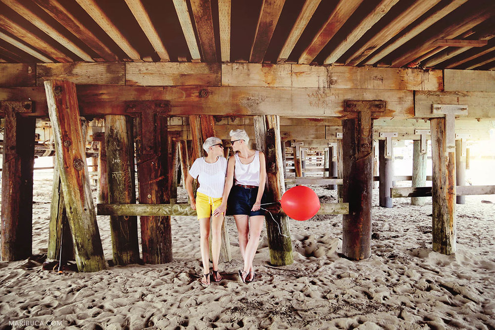 Two girls with sunglasses and the red balloon stay under the old wooden bridge speaking each other.