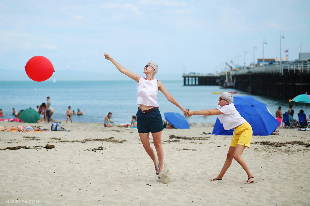 Wedding images of two girls try to make the red balloon fly and they have fun in the beach, Santa Cruz