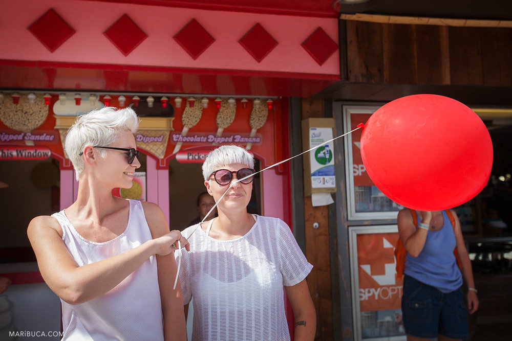 Girls have fun with red balloon during their wedding walk in the Boardwalk's Cocoanut Grove, Santa Cruz .