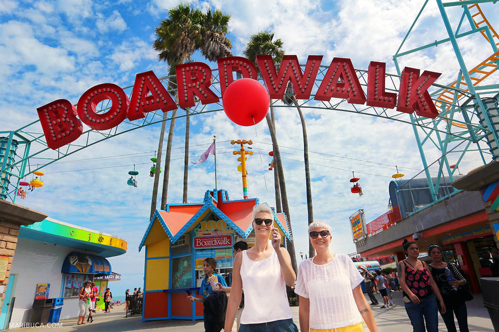 "girls with short haircuts, sunglasses, white t-shirts, one of them holds a flying red ball against the background with sign  ""Boardwalk"" in an amusement park in Santa Cruz."