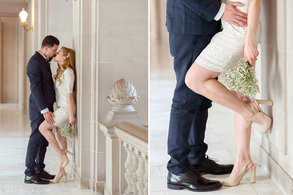 the groom leaned the bride against a pole and gently is touching her leg and they are kiss each other in SF City Hall. Wedding element: groom's dark blue pants of the groom who touches the waist of the bride leaning against the wall and leaning one leg against the pole.