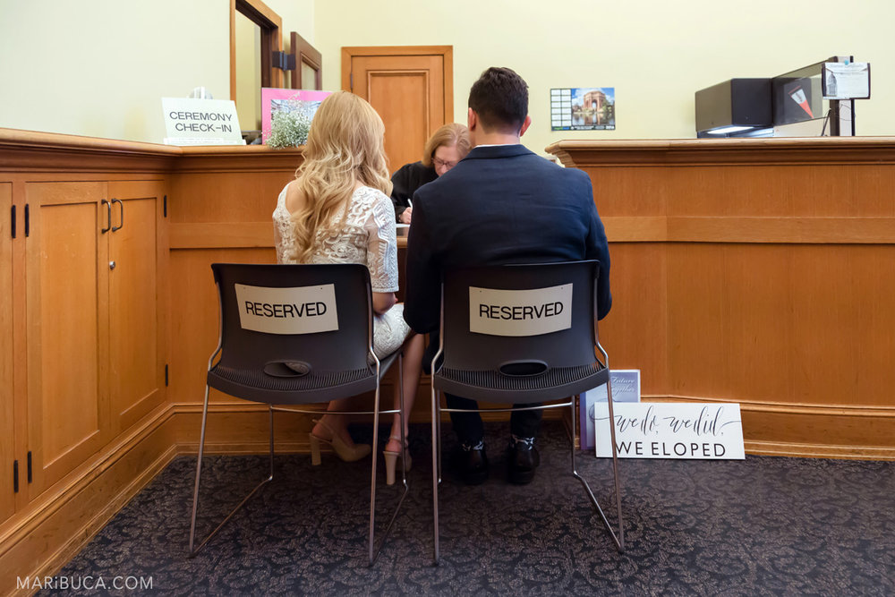 "before ceremony couple went to register office and sit in the black chairs with sign titles ""Reserved"" in san francisco city hall"
