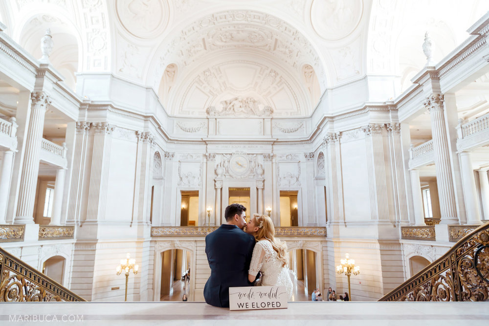 Sign we do, we did, we eloped! The bride and the groom are sitting in the stairs and kissing each other