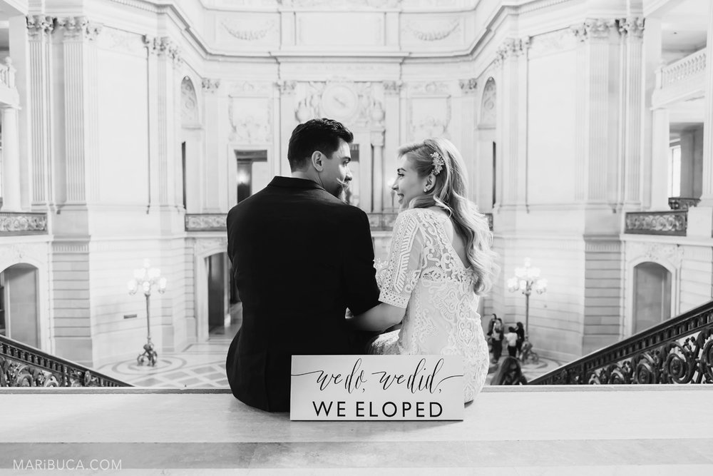 "Black and white photo. Just married couple look each other with happy faces, in front of them the white sign ""We do, we did, WE ELOPED""."
