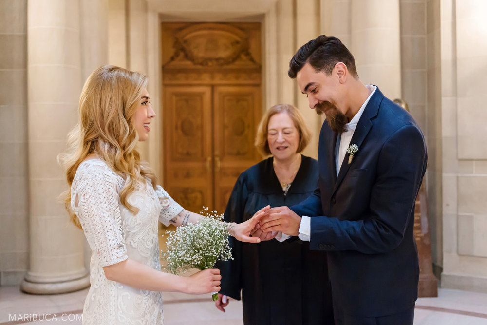 THe bride and the groom exchange of rings during the wedding ceremony in the SF City Hall..