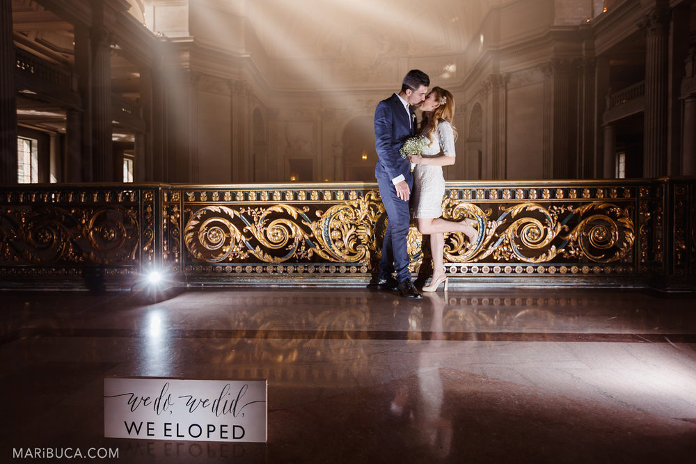 "the bride and groom kiss each other and in front of them is a sign ""we do, we did, we eloped"" with rays of light from the window on the second-floor balcony with a magnificent view of San Francisco City Hall and the morning rays from the windows."
