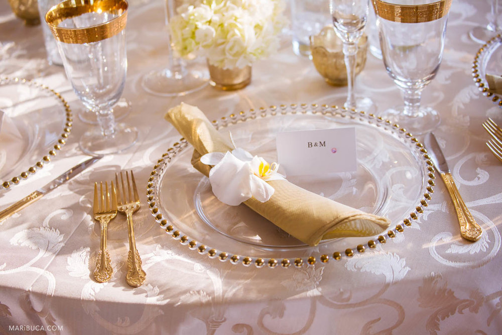 Wedding details during reception in the table: whitecloth, nice cards, golden silvers, wine glasses