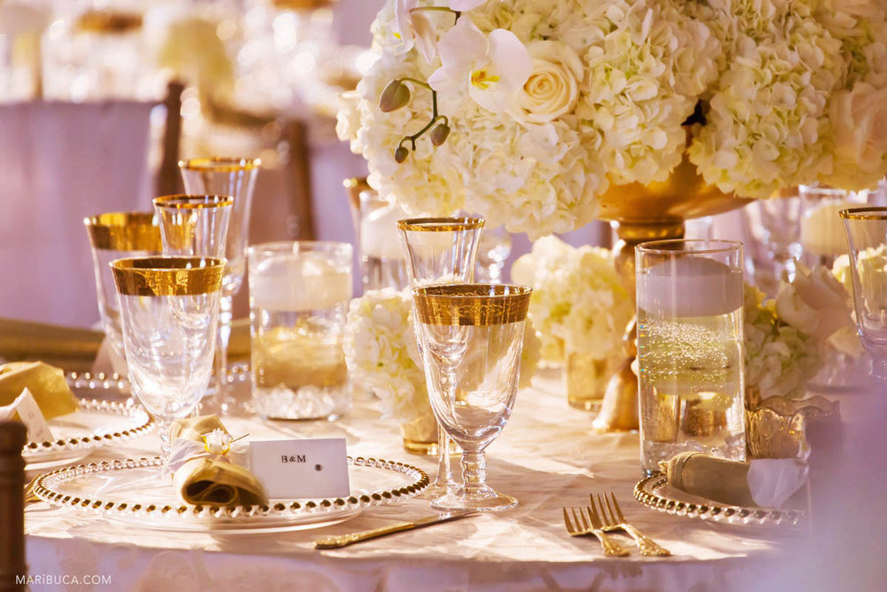brilliant and sunny table decorated with white flowers in a vase, wine glasses with gold trim and cutlery for the wedding.