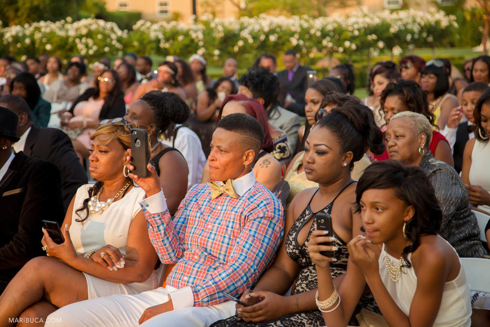 Guests are sitting and listening the wedding ceremony during sunset time.